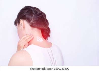 The girl smears her neck with a healing cream to relieve muscle tension and pain. Treatment of cervical spinal diseases, copy space