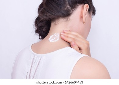 A girl smears a neck with a healing and anti-inflammatory ointment to relieve muscle stiffness and pain, close-up, neuralgia