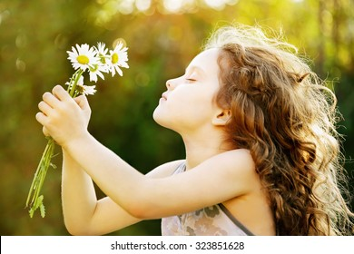 Girl smelling a bouquet of daisies, photo in the profile. Healthy breathing. Instagram toning, sunset light.