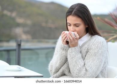 Niña oliendo su café sentada en una terraza de café en un lago en la montaña