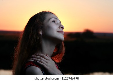 girl with a smile on her face against the setting sun