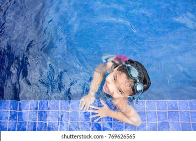 girl smile while swimming in pool clear and clean blue water, cute kid hang at corner of pool, text copy space