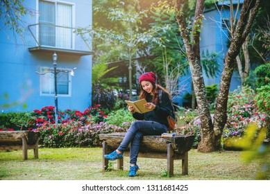 The girl smiled and was happy with the book she read. Read a book in the flower garden.