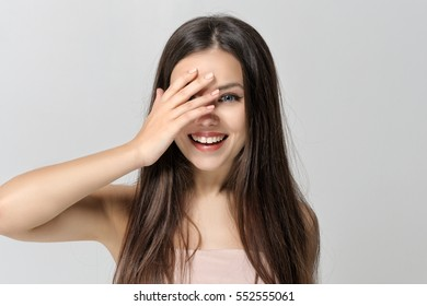 Girl smiles and covers her eyes with her hand. She has a clean well-groomed skin and long brown hair. Close-up portrait against a light gray background.