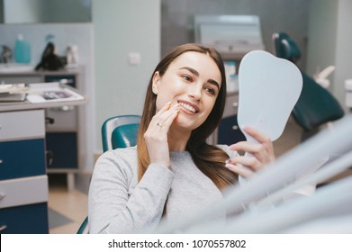 The girl smiles in dentistry. patient dentist racing model at the Dental Clinic. White well-groomed teeth after taking a doctor. Tooth whitening and tooth enamel. In the hands of the mirror