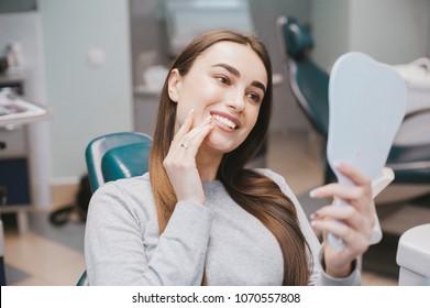 Het meisje lacht in de tandheelkunde. patiënt tandarts race-model bij de Dental Clinic. Witte, goed verzorgde tanden na het nemen van een arts. Tanden bleken en tandglazuur. In de handen van de spiegel