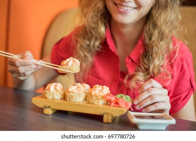 The girl smiles and eat Japanese food keeps sushi rolls with wooden chopsticks and moka them in soy sauce