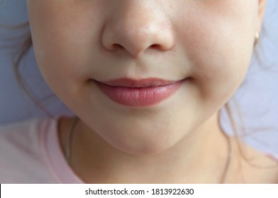 The girl smiles with her mouth closed. Close-up of a child's face.