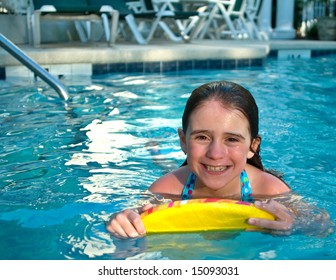A girl smiles as she swims in the pool.