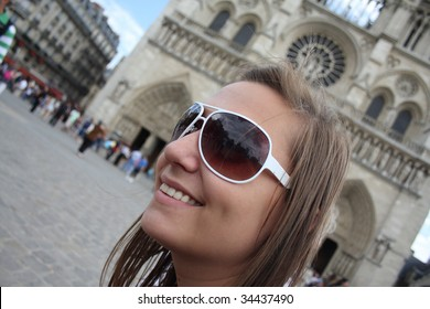 Girl smiling and enjoying her city trip in front of the Notre Dame
