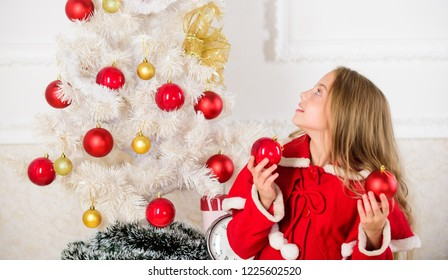 Girl smiling face hold balls ornaments white interior background. How to decorate christmas tree with kid. Let kid decorate christmas tree. Favorite part decorating. Getting child involved decorating.