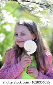 Girl with smiling face on nature background, defocused. Childhood, sweets and natural beauty concept. Schoolgirl with candy walks outside near blooming trees. Kid in pink sweater holds white lollipop.