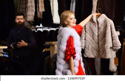 Girl with smiling face wearing white mink fur. Expensive shopping concept. Couple in love shopping in fur mall. Woman in white fur coat with worried bearded macho behind her looking for new overcoat.