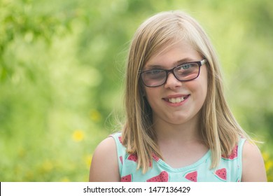 girl smiling with a green blurred background while wearing glasses