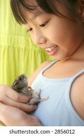 Girl smiling happily and playing with her grey pet hamster