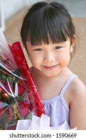 girl smiling & holding bouquet of red roses