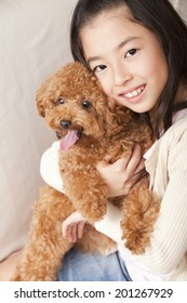Girl smiling and hugging toy poodle