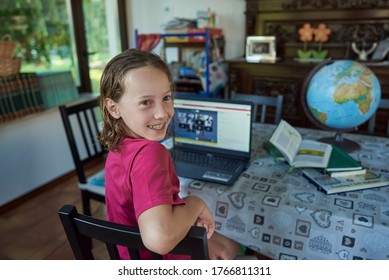 Girl smiling infront of the laptop at her home