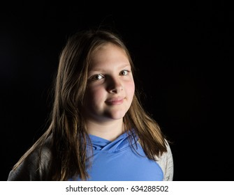 Girl smiling and looking at the camera over black  background