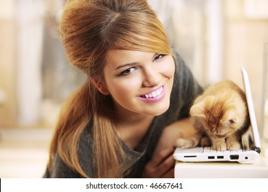 girl smiling next to kitten on laptop inside a beautiful home