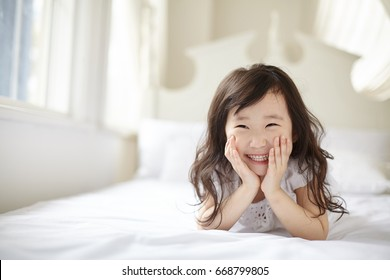 A girl smiling on a bed