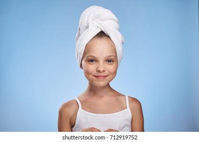 girl smiling on head towel on blue background portrait, beauty