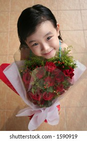 girl smiling, standing & holding bouquet of red roses