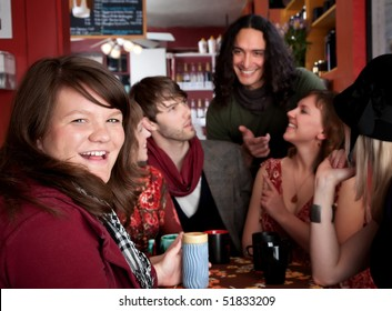 Girl smiling at table with friends in coffee house
