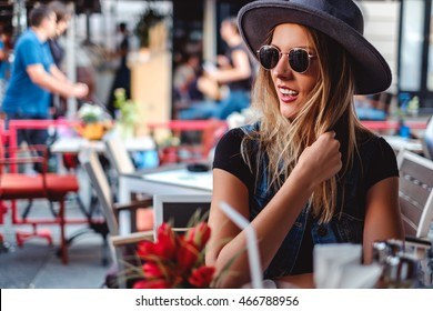 Girl smiling while sitting in a coffee shop and looking to the side