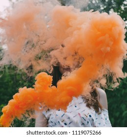 Girl with smoke bomb makes colorful clouds of smoke.