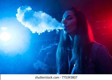 The girl smokes a cigarette and lets out smoke in a nightclub. The neon light shines here. The girl is standing alone.