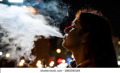 The girl smokes an electronic cigarette against the backdrop of the night city. Woman enjoying vape, nicotine steam vaporizer. Bad habit.
