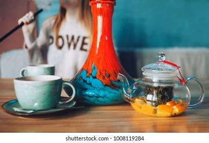 A girl smokes a hooka. A tea-pot, mug, stands on a table