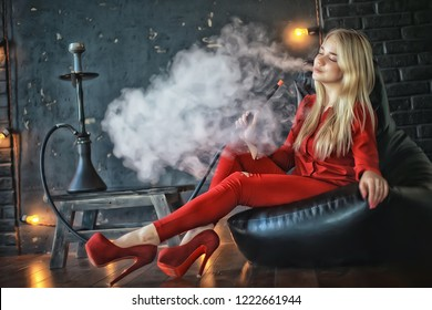 girl smokes  hookah / beautiful glamorous girl in red dress smokes a hookah, the sexy model in a night club smokes