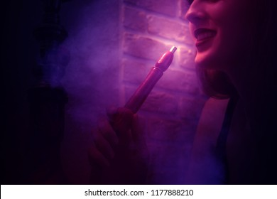 The girl smokes a hookah. Dark ultraviolet abstract background with smoke