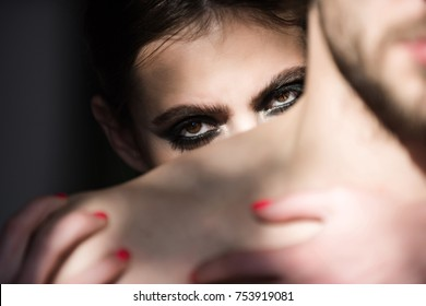 Girl with smokey eyes, makeup face. Macho with naked shoulder. Woman look out behind man. Couple in love. Relationship, care concept.