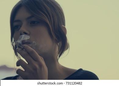 girl smoking a cigarette thinking