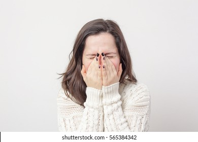 Girl sneezes, covering her face with with hands. To be afraid of something and turn a blind eye
