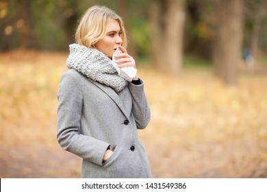 Girl sneezing in tissue. Young woman blowing her nose on the park. Woman portrait outdoor sneezing because cold and flu