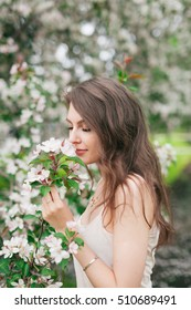 Girl sniffing cherry flowers tree in park