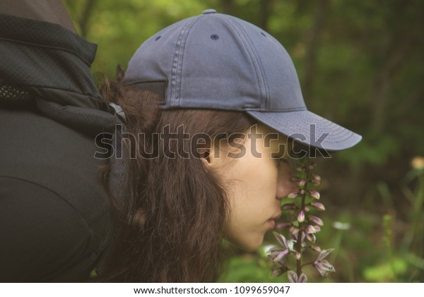 The girl is sniffing flowers in the mountains. Trekking