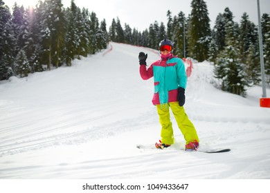 girl snowboarder in gear stands on a slope in the forest and waves her hand smiling