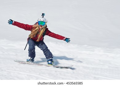 girl snowboarder goes quickly down the slope and shouts his arms to the side