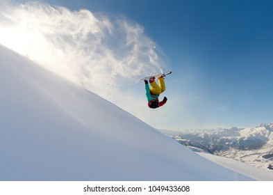 girl snowboarder jumping front flip leaving behind a wave of snow