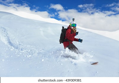 girl snowboarder rides fast on loose snow Freeride