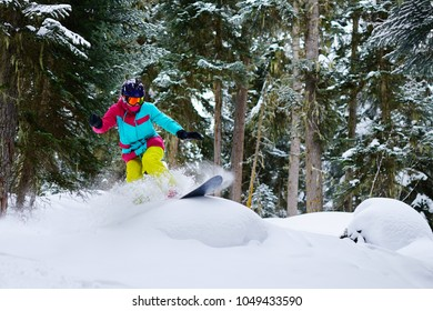 girl snowboarder rides freeride on powder snow in the forest