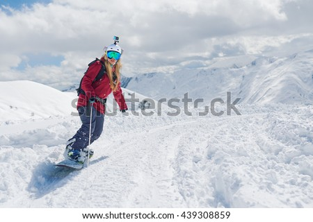 girl snowboarder rides a snowboard towed holding the rope.
