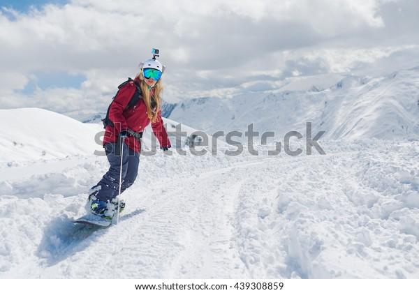Mädchensnowboarder fährt mit einem Snowboard, das das Seil hält.