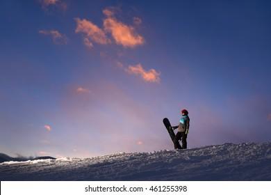 Girl snowboarder stands on a hillside against the dark sunset sky