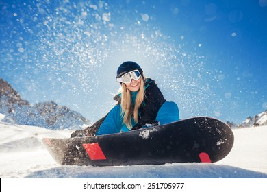 girl snowboarding in the mountains on the snowboard
